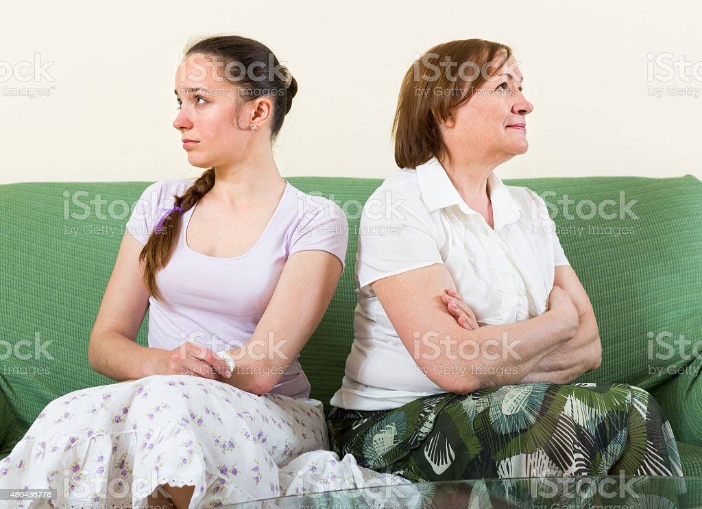 Sad daughter against  mother stock photo