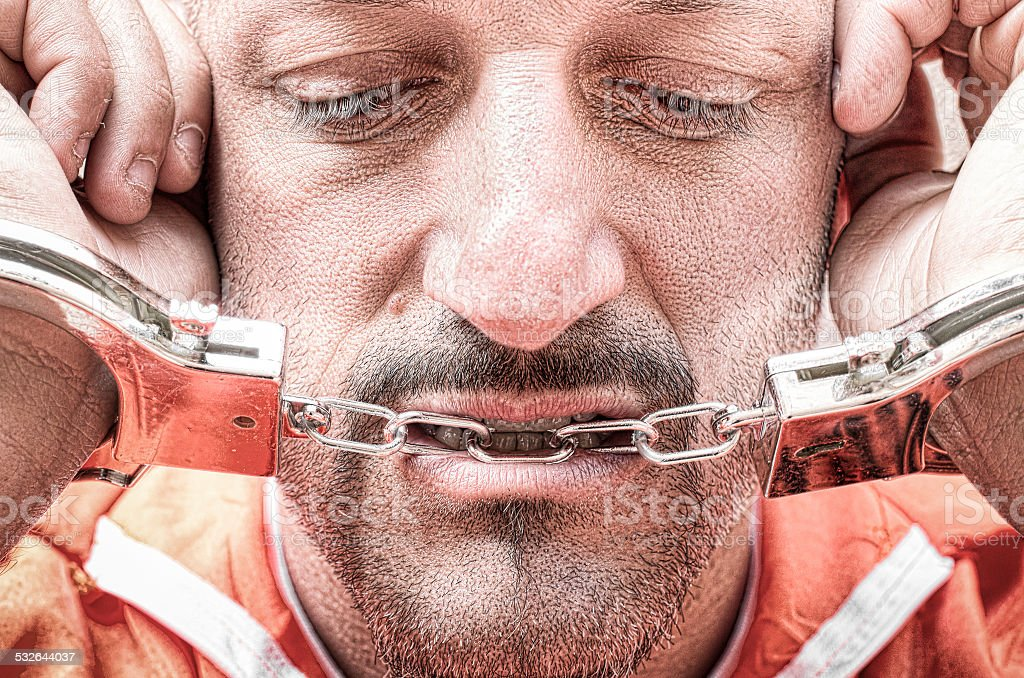 Sad depressed detained man with handcuffs in prison stock photo