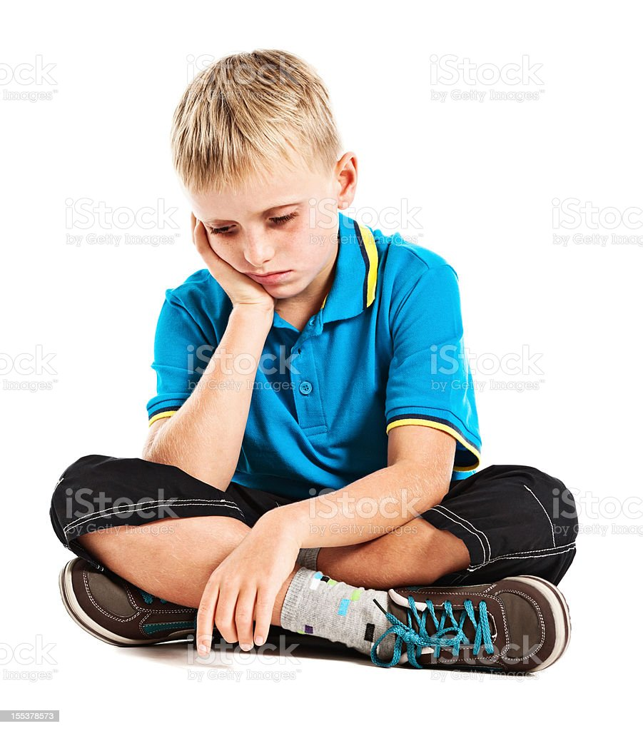Sad, depressed or sick boy looks down stock photo