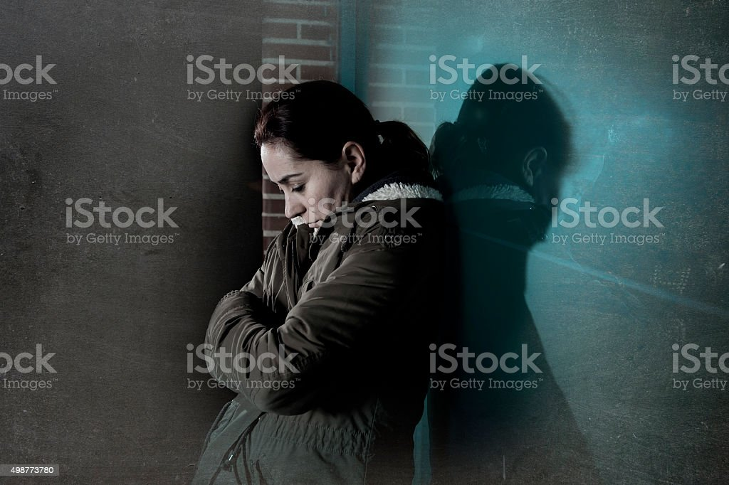 sad depressed woman alone leaning on street window at night stock photo