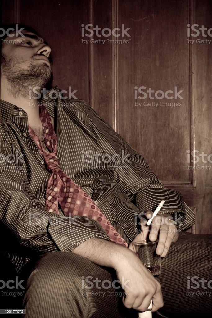 Sad, Disheveled Businessman Drinking and Smoking stock photo