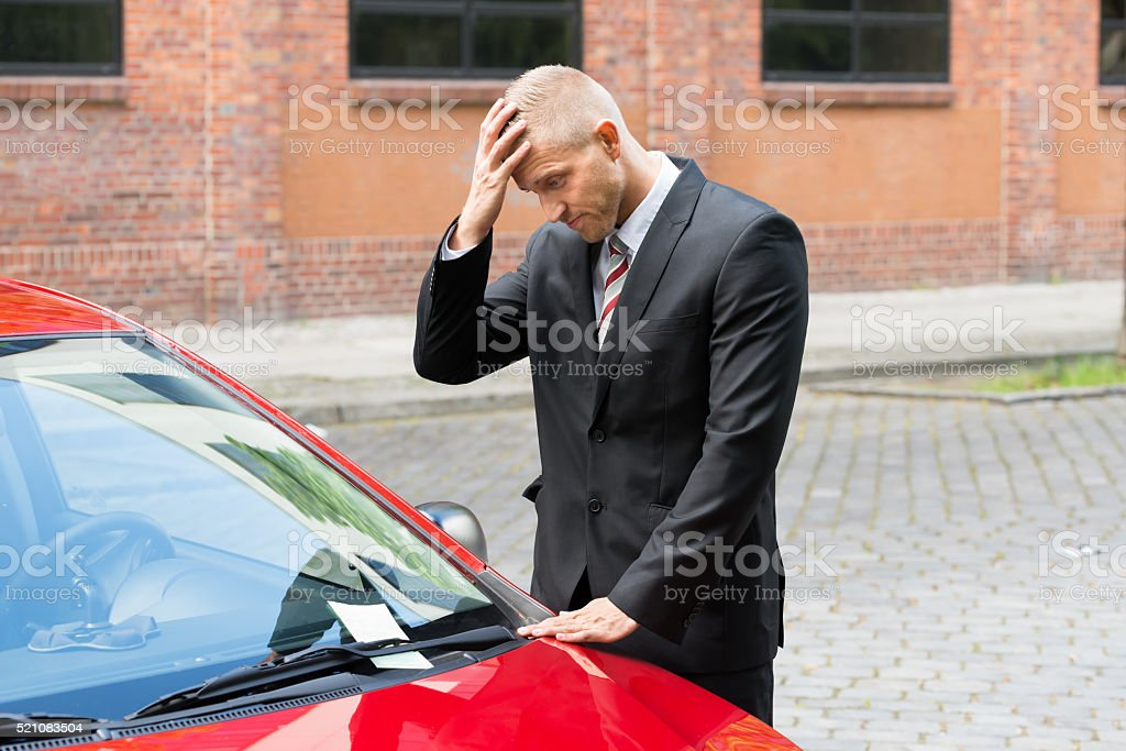 Sad Driver Looking At Parking Ticket On Car stock photo