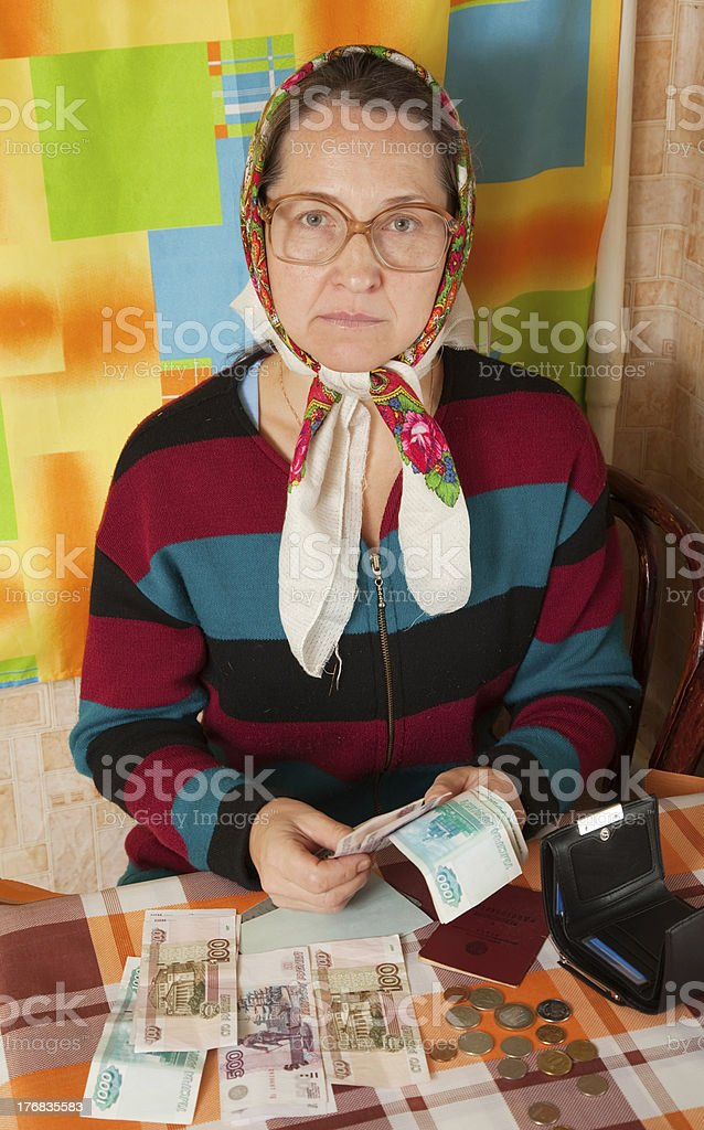 Sad erderly woman with money stock photo