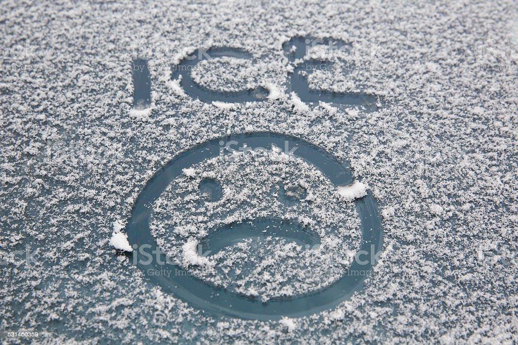 Sad face drawn on windshield stock photo