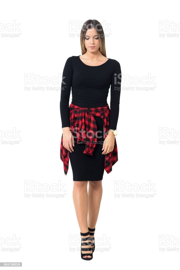 Sad feminine woman in black dress walking and looking down. stock photo