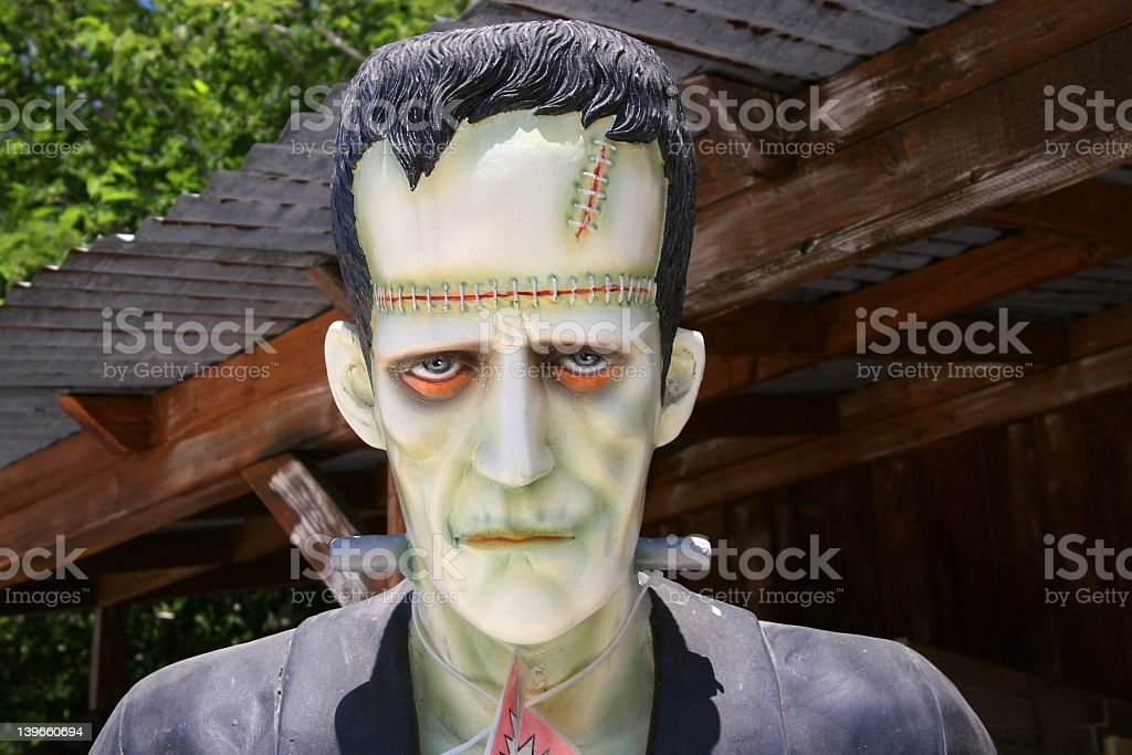 Sad Frankenstein monster standing in front of shed stock photo