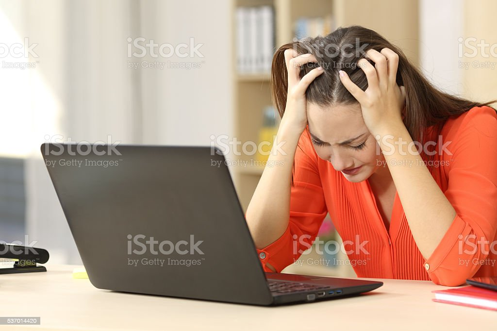 Sad freelancer working with a laptop stock photo