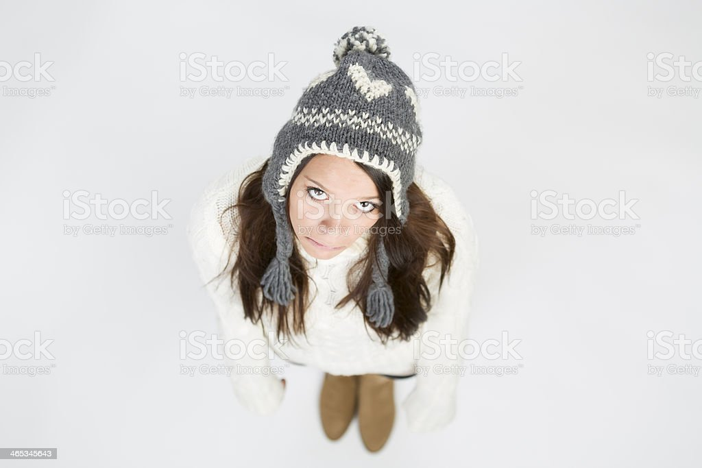 Sad girl in winter pullover and cap looking up. stock photo