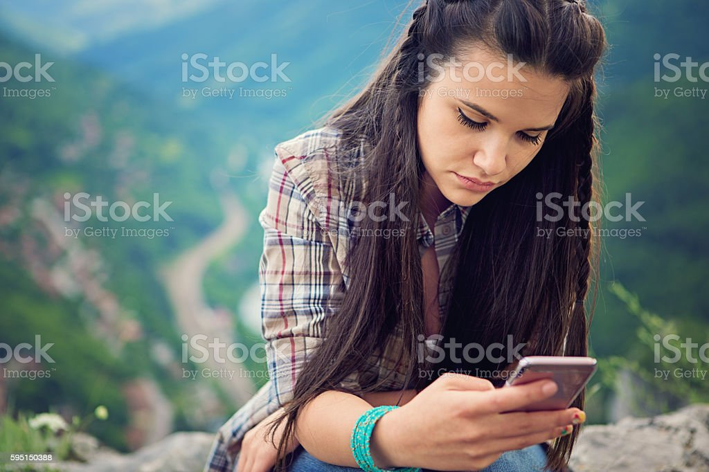 Sad girl is texting using her mobile phone stock photo