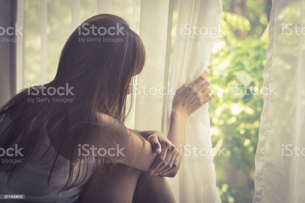 Sad girl looking out of window stock photo
