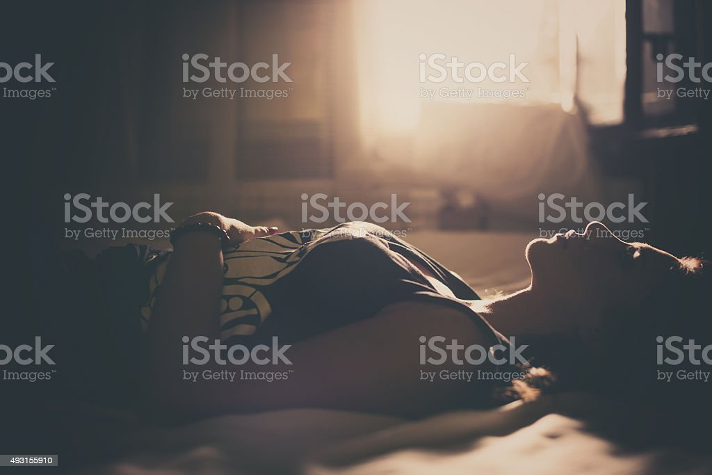 Sad girl lying in bed stock photo