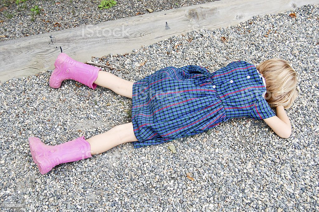 Sad girl lying on the ground stock photo