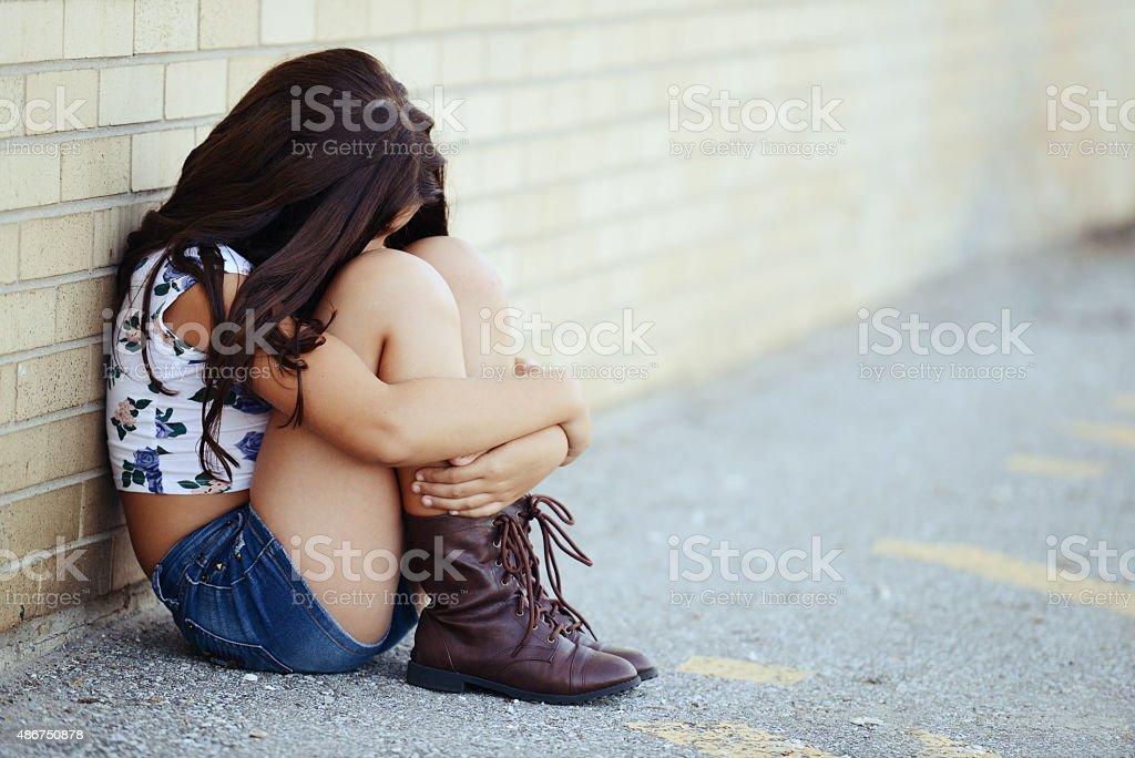 sad girl sitng by brick wall stock photo