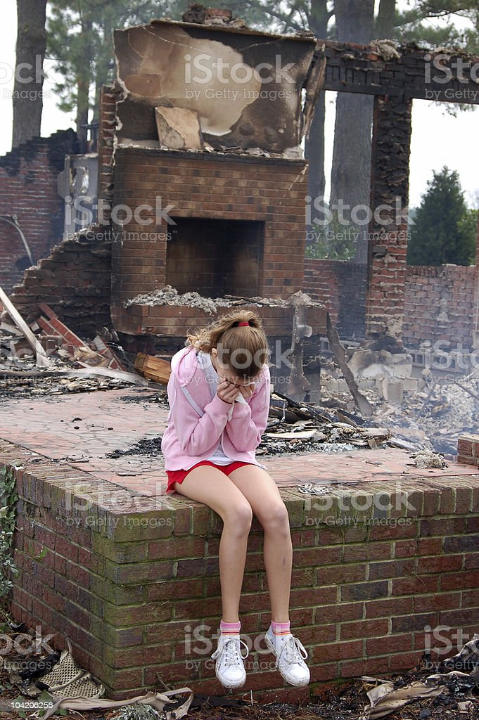 Sad girl sitting in a ruined place on a brick stage stock photo