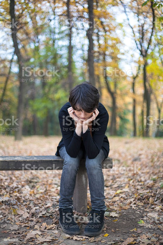 Sad girl sitting on a bench royalty-free stock photo