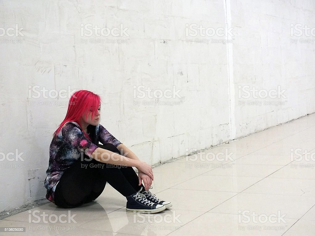 Sad girl sitting on the floor stock photo
