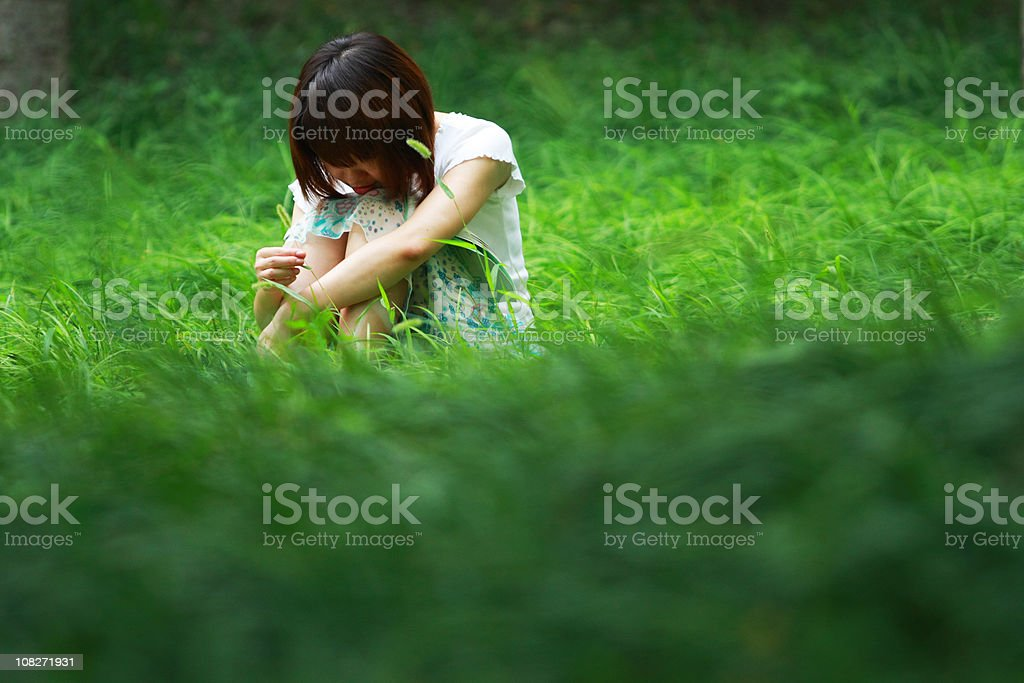 sad girl sitting on the grass royalty-free stock photo