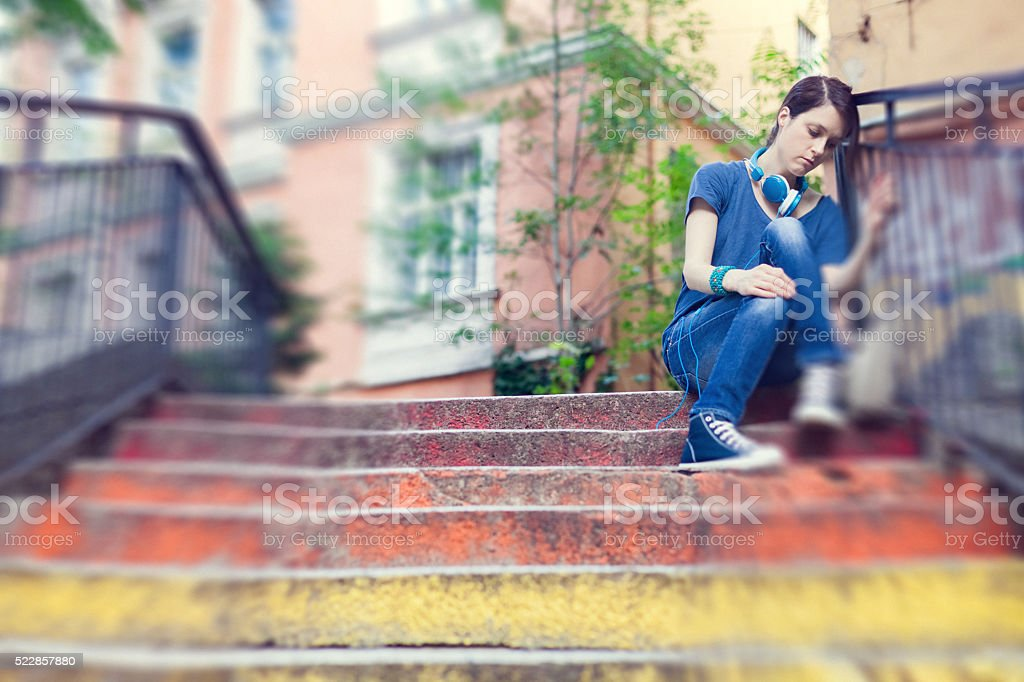 Sad girl sitting outside at the street stock photo
