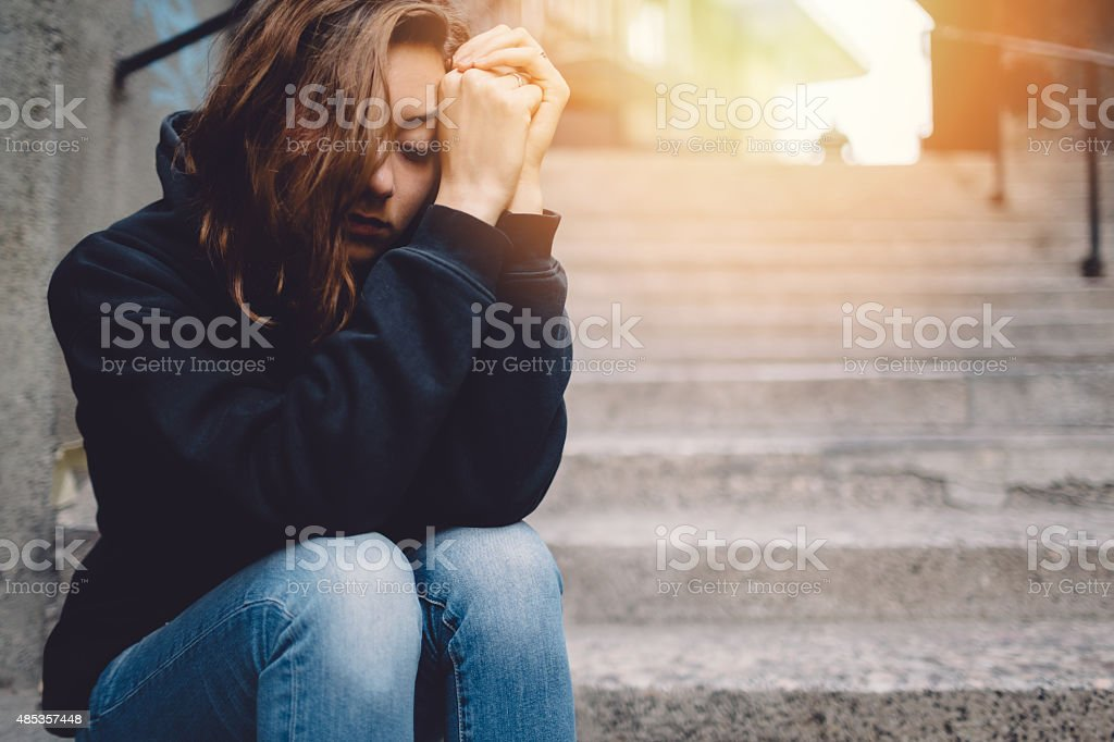 Sad girl sitting thoughtfully at the street stock photo