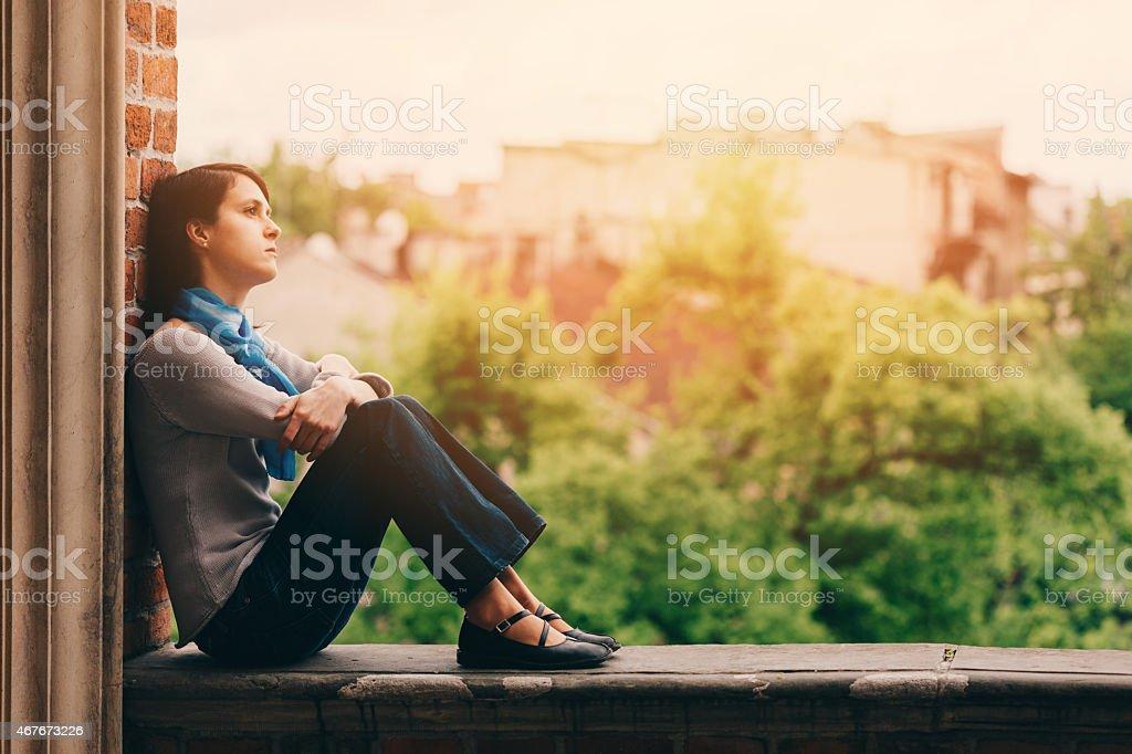 Sad girl sitting thoughtfully outside stock photo