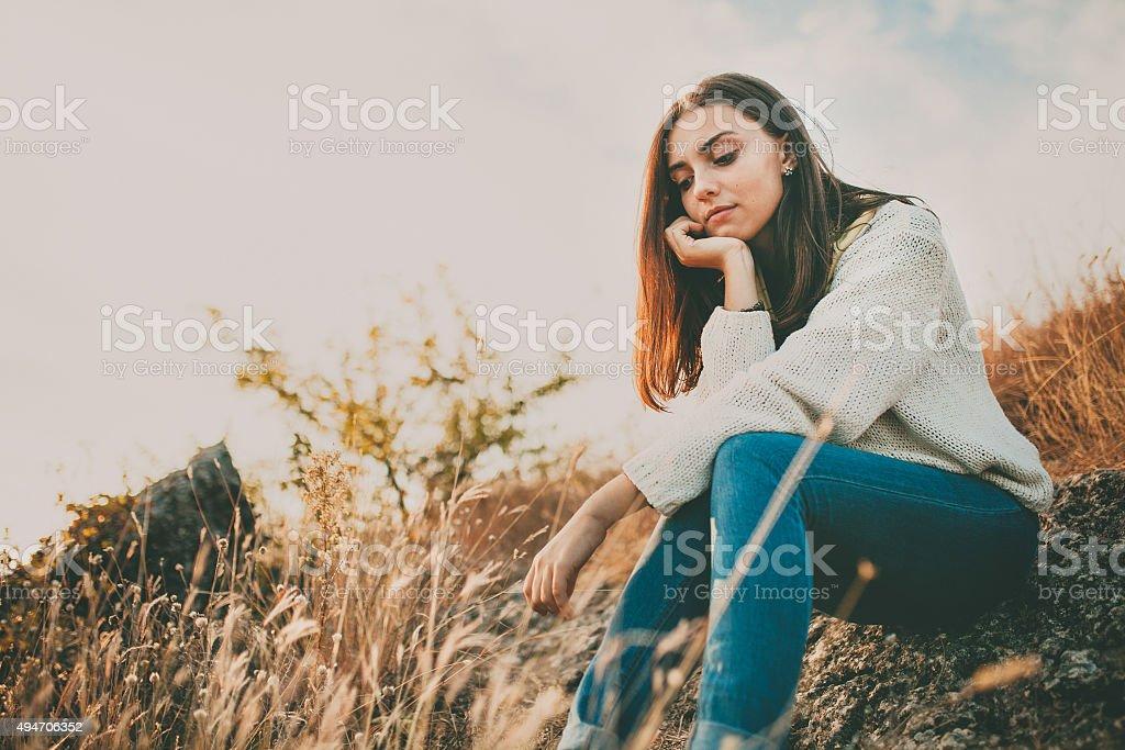 Sad girl thinking outdoors stock photo