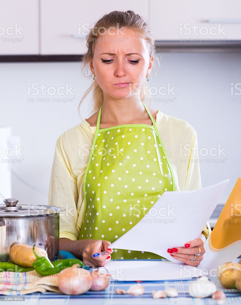 Sad girl with banking statement at home stock photo