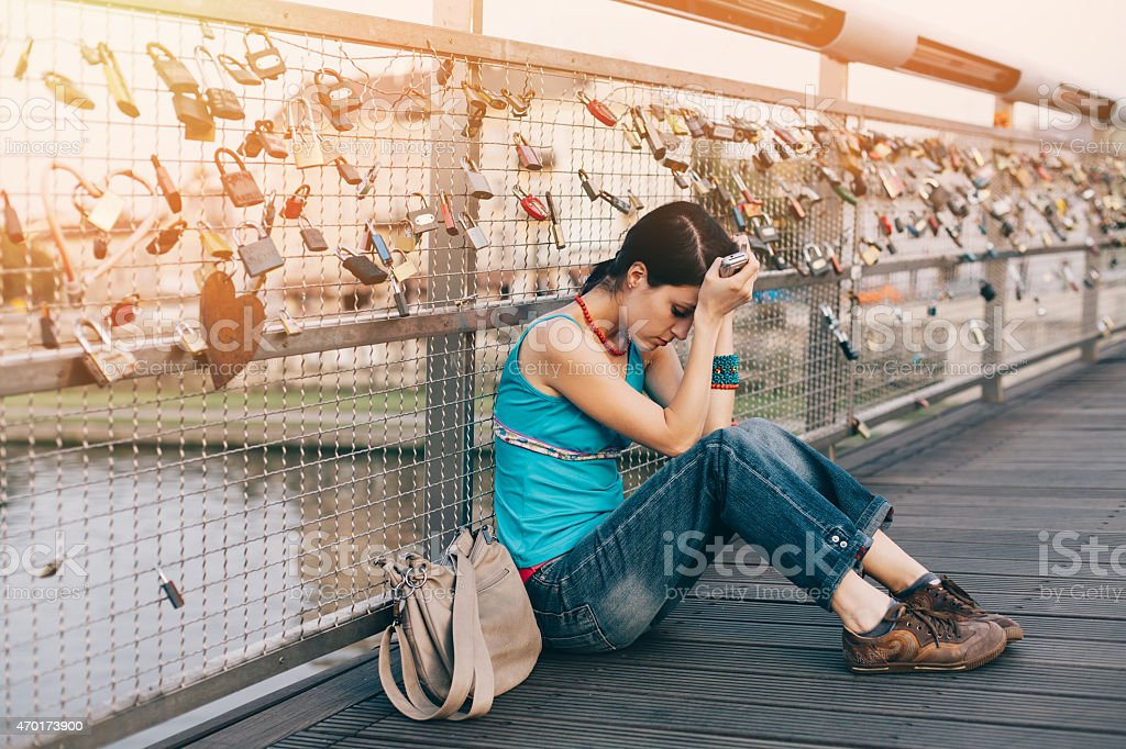 Sad girl with head in hands outside stock photo
