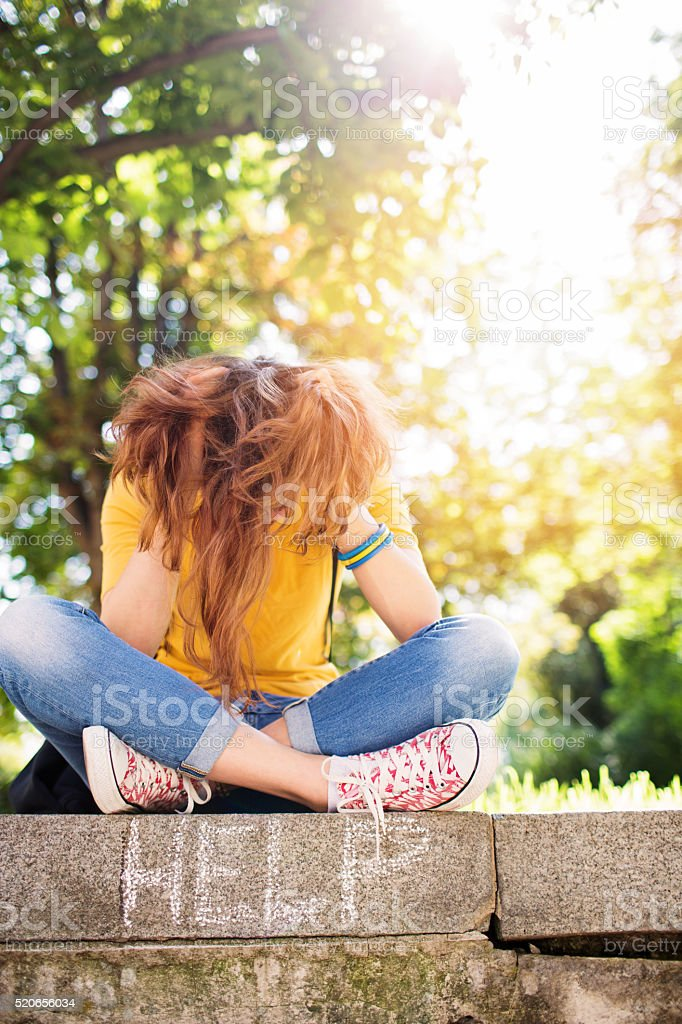 Sad girl with head in hands stock photo
