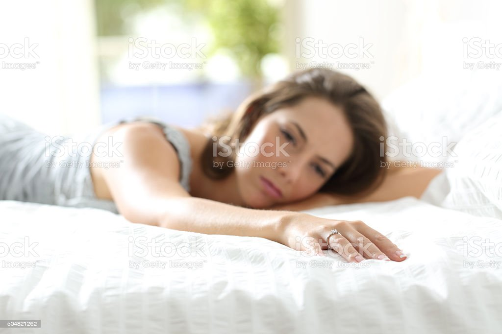 Sad girlfriend missing her boyfriend on the bed stock photo