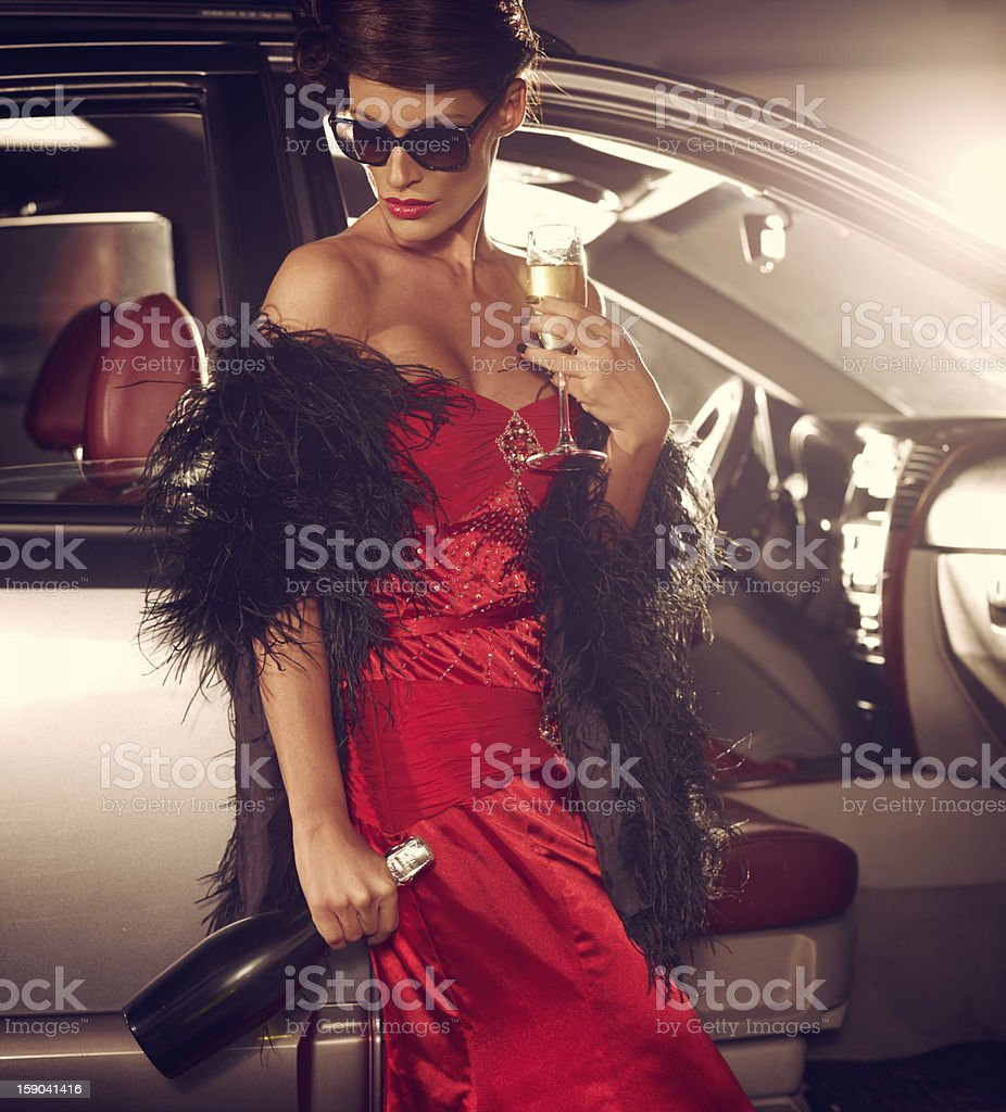 Sad Glamorous Woman Standing Next To Luxury Car With Champagne stock photo
