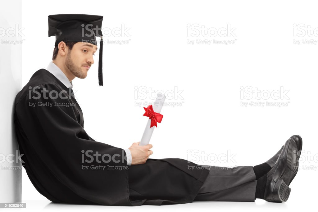 Sad graduate student with a diploma sitting on the floor stock photo