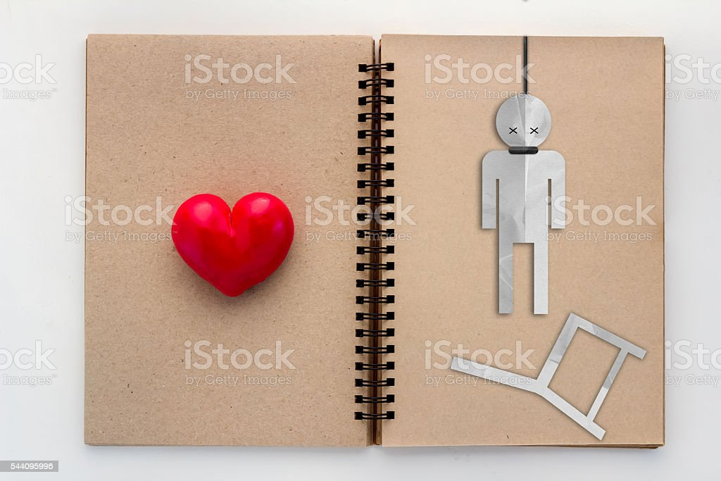 sad hangman witth red heart on blank page recycle notebook stock photo