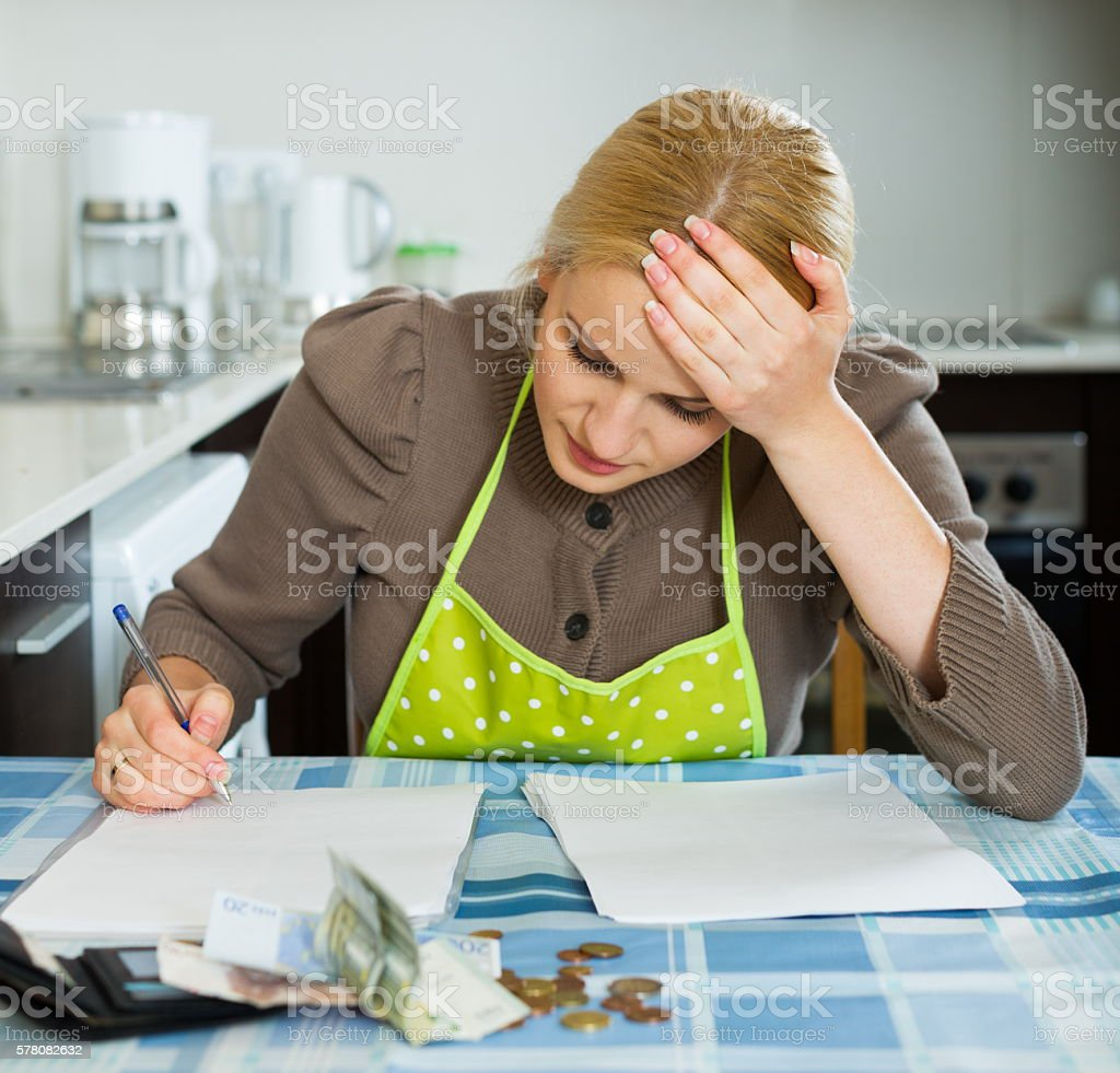 Sad housewife filling payments bills stock photo