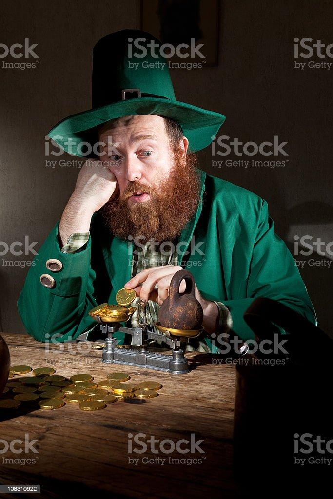 sad leprechaun count coins stock photo