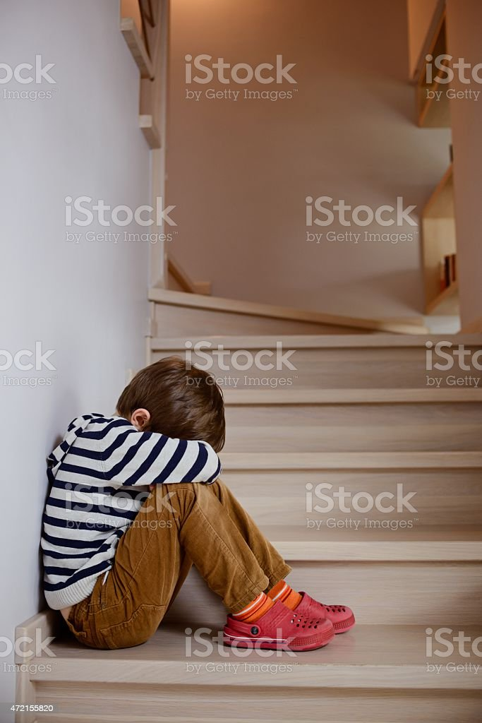 Sad little boy crying depressed sitting stock photo