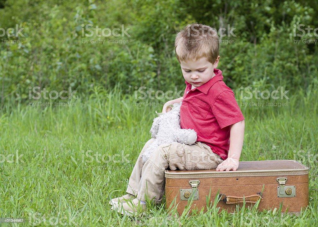 sad little boy with suitcase and stuffed animal stock photo