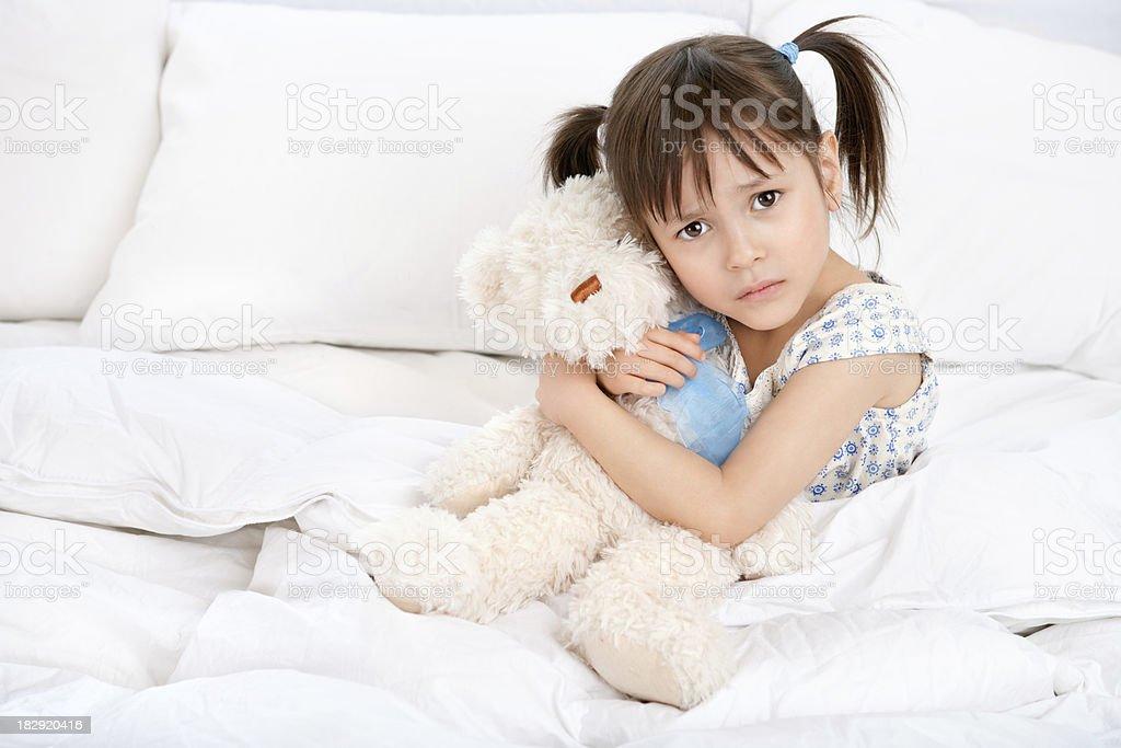 Sad little girl hugging teddy bear in bed royalty-free stock photo