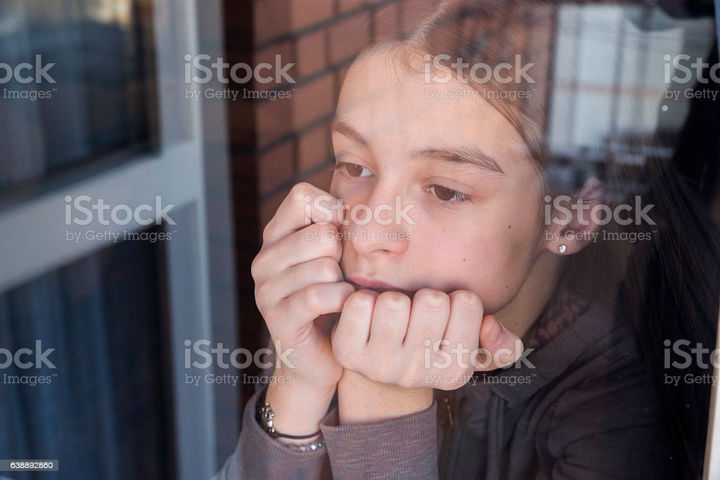 Sad little girl looking out the window stock photo