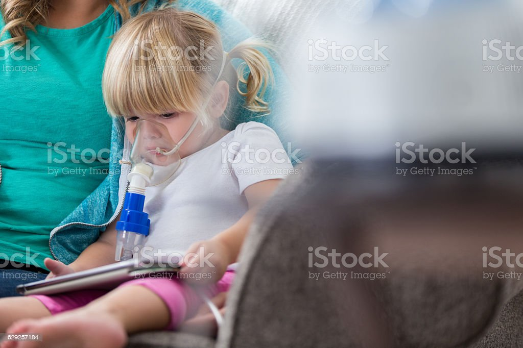 Sad little girl receives breathing treatment at home stock photo