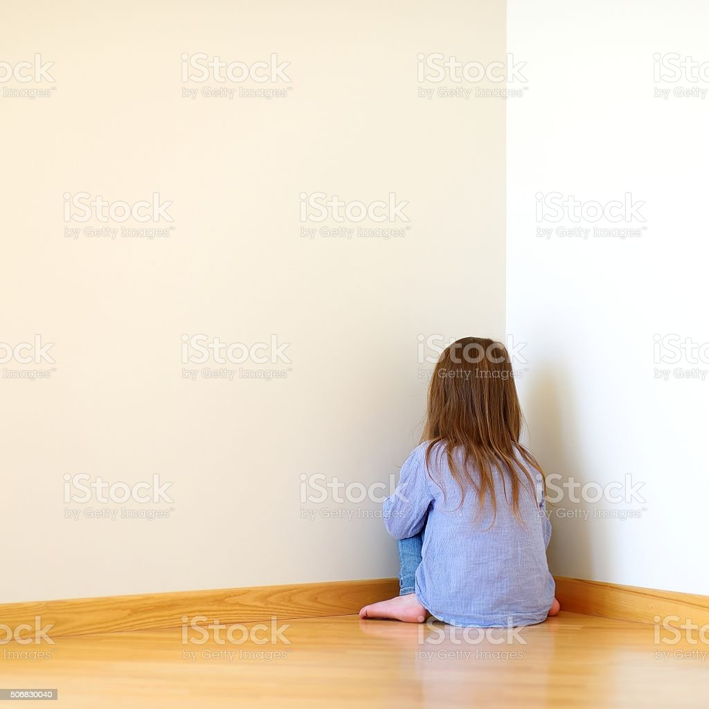 Sad little girl sitting in a corner stock photo