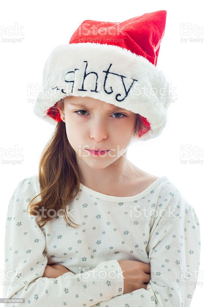 Sad little girl wears 'Naughty' Santa hat at Christmastime stock photo