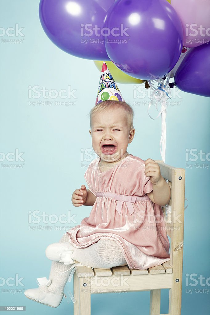 sad little girl with cap and balloons stock photo