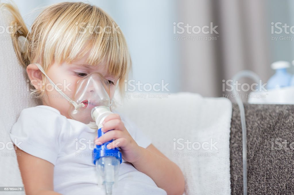 Sad little girl with cystic fibrosis receives breathing treatment stock photo
