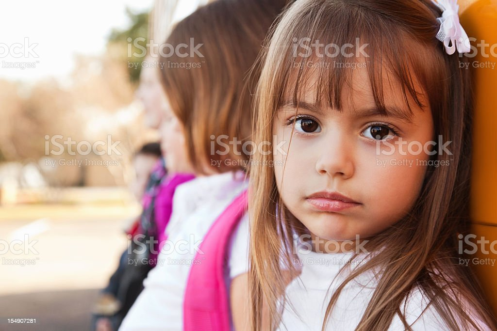 Sad Little Girl With Other Students at School Bus stock photo