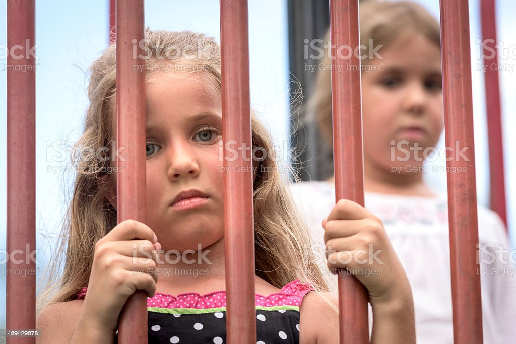 Sad Little girls in a cage stock photo