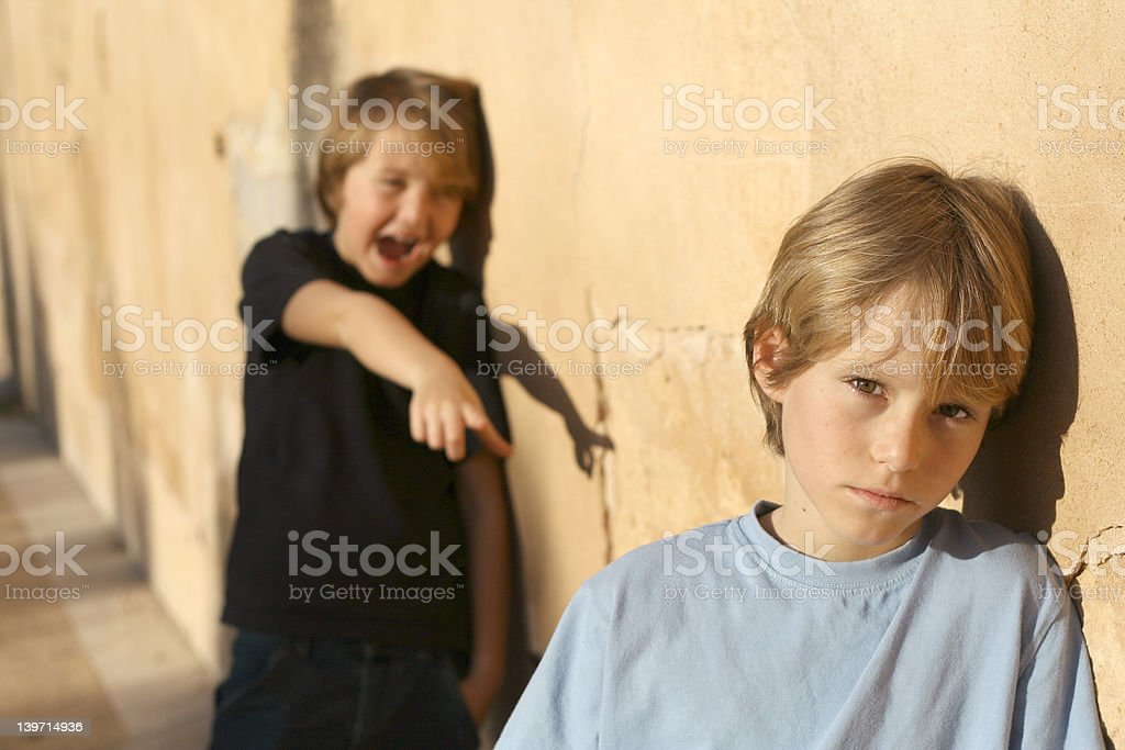 sad lonely child being bullied by school bully royalty-free stock photo