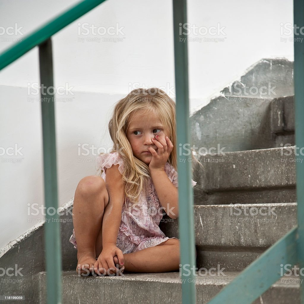 Sad lonely girl sitting on stairway royalty-free stock photo