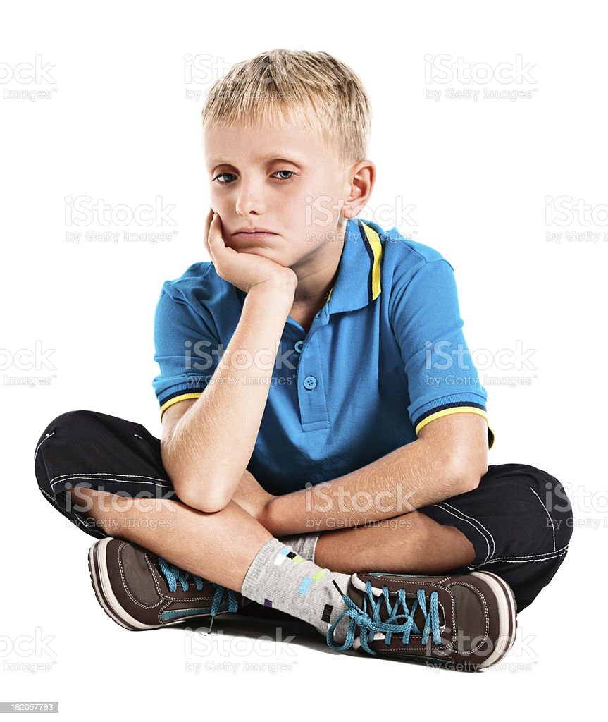 Sad looking 9 year old boy seems withdrawn and unhappy. stock photo