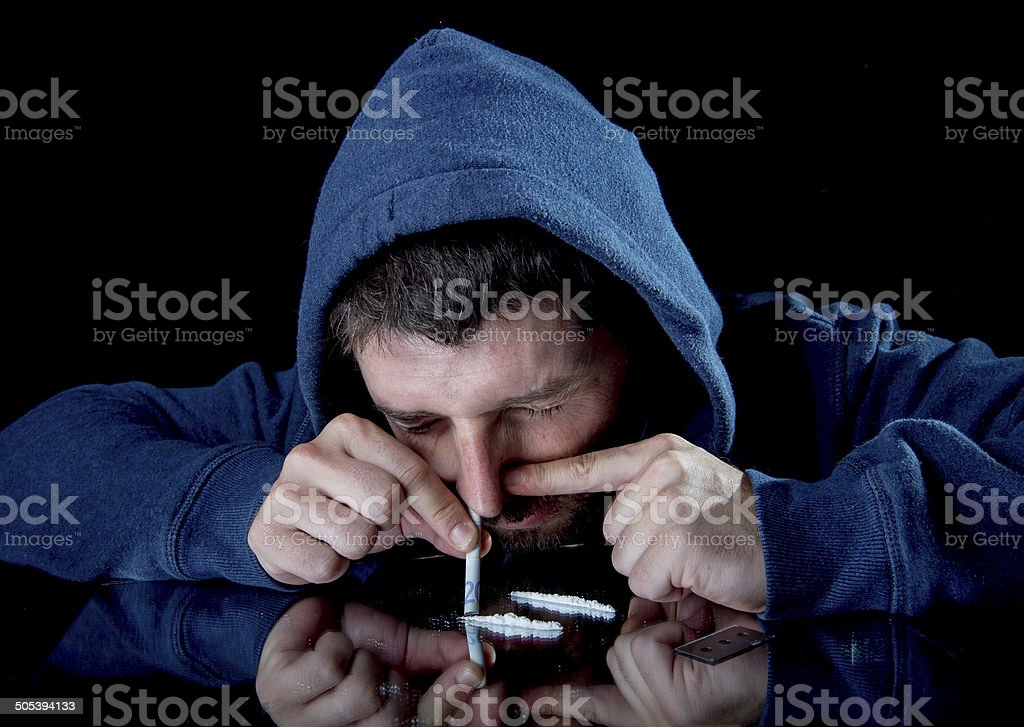 sad man doing sniffing cocaine at home on his own stock photo