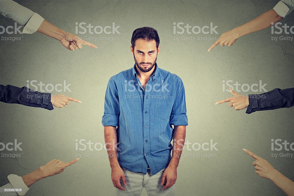 Sad man looking down many fingers pointing at him stock photo